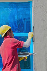 A professional stucco contractor installing stucco near the window in a house in Windsor, ON